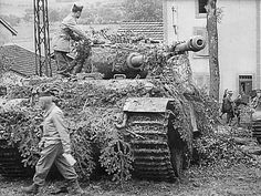 A Panther Ausf G that was left abandoned is getting a look over by American personnel