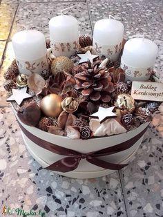 A háncs dobozt kibéleltem száraztűzőhabbal majd ebbe állítottam bele a fehér gyertyákat. Ezután körbe díszítettem karácsonyi üveg gömbökkel, termésekkel, mini toboz, bakuli termés, natúr lali, mahagony, casurina is díszíti a doboz belsejét. Mintás szalagot tettem a gyertyákra,szatén szalagot kötöttem a dobozra.Végül Boldog karácsonyt táblát tettem rá. November utolsó vasárnapja advent első vasárnapja onnantól kezdve az ünnepvárás része lehet az asztaldísz egészen vízkeresztig. . Mérete…