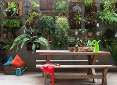 Os publicitários André Eyer e Beatriz Molinari criaram juntos o jardim suspenso com plantas dispostas em painéis de fibra de coco. Ao lado da churrasqueira, a mesa de madeira da Tok & Stok é usada pelo casal de moradores para reunir família e amigos.