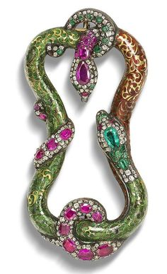 A late 19th century enamel and gem-set buckle The openwork cartouche formed of two writhing serpents, one with green enamel floral body, vari-cut emerald and diamond head and tail and ruby eyes, the other with terracotta enamel floral body, cushion and pear-shaped ruby and cushion-shaped and rose-cut diamond head and tail with emerald eyes, closed-back settings throughout
