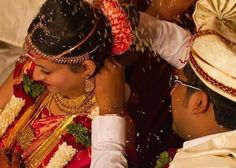 """A mangala sutra (from Sanskrit mangala, meaning """"holy, auspicious"""", and sutra, meaning """"thread"""") is a necklace that a Hindu groom ties around the bride's neck in a ceremony called Mangalya Dharanam (Sanskrit for """"wearing the auspicious""""), which identifies her as a married woman."""