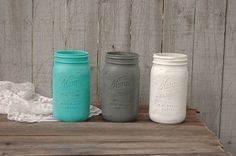 Hand painted and distressed mason jars in aqua, grey and white, with a protective coating. They are not painted on the inside and can hold water for fresh flowers. Clean with a damp cloth, not dishwas