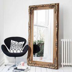 Роскошная золотистая рама, белые стены, черные акценты в мебели.