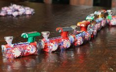 CANDY CHOO CHOO TRAIN!!!!!  Start with a package of gum. Clove gum because it was red.(FOR ENGINE)  Hot glue 1 roll of Lifesavers to the pack of gum letting the Lifesavers hang over 1 end of the gum.  Add 1 foiled Rolo.  Add 1 Hershey's miniature candy to the top of the Rolo.    Add 1 upside down foiled Hershey's Kiss.  Add 4 wrapped peppermint discs.  A train and to add more car, just repeat the process