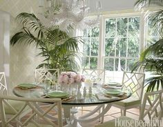 """""""This room really sparkles during the day, between the glass of the window and the glass on the table,"""" Braff says. The """"coral"""" chandelier mimics the curves of the Regency Center table by Niermann Weeks, set with Dodie Thayer Lettuce Ware. Fretwork side chairs from Hickory Chair can be customized to your color. Sea Island Trellis wallpaper by Brunschwig & Fils."""