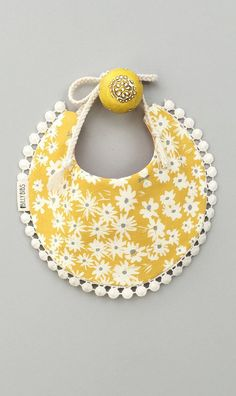 The Adeline bib comes with a crosshatch dusty pink fabric on one side, and a mustard daisy design on the other. It is trimmed with a cotton pom pom lace and has natural cotton string ties. This is a p