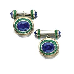 PAIR OF SAPPHIRE AND EMERALD CUFFLINKS. Each bezel-set with an oval sapphire bordered by calibré-cut emeralds, to the bar set with similar stones and sapphire terminals, mounted in yellow gold and platinum.