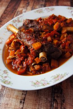 Goat Shanks with Harissa, Tomatoes, and Carrots over butternut squash puree. A healthy paleo meal that is easy to make in the slow cooker!