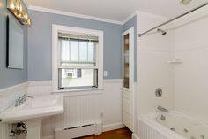 Cottage Full Bathroom with Wainscoting, Hardwood floors, Drop-In Bathtub, Crown molding, High ceiling, Pedestal Sink