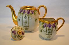 Limoges Oval Shaped Teapot And Creamer With Hand Painted Purple Violets Nestled Among Green Leaves In A Panel Motif, Marked William Guerin Limoges France   c.1910-1912