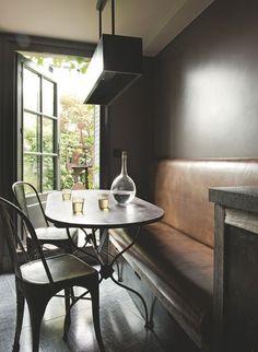 Banquette en cuir et table en métal dans la salle à manger ouverte sur la terrasse. Plus de photos sur Côté Maison http://petitlien.fr/84pe