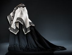 1897 Reception Gown: On the death of her husband Prince Albert in 1861, Queen Victoria chose to wear widow's mourning clothes for the rest of her life. This formal gown and cape was designed for her in 1897, the year of her Diamond Jubilee, celebrating sixty momentous years on the throne. It is made of somber black materials: faille and crêpe. Only a long train and scattered embellishments of silk lace and metal spangles are a concession to required royal grandeur.