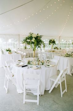 White and sage green reception decor. Tent wedding reception with a string of lights. Gold wedding accents. Photography by Kina Wicks.