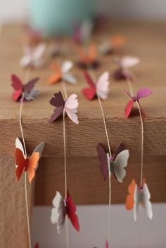 Each butterfly has been hand glued onto the string (back-to-back with a different colour), with a little bead between each one.