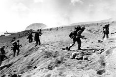 U.S. Fourth Division Marines move in from the beach on Iwo Jima, on Feb. 19, 1945. A dead Marine lies at right in the foreground. Mt. Suribachi, in the background, was turned into a beehive of guns by Japanese troops. It was scaled by the U.S. Marines, who took control.