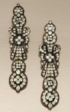 PAIR OF SILVER, GOLD AND CHRYSOBERYL PENDENT EARRINGS, PORTUGUESE SECOND HALF OF THE 18TH CENTURY.  Each centring on a stylised tied ribbon bow, suspending two graduated interlocking circular motifs, each centring on a quatrefoil, to a similar surmount, set throughout with foil backed mixed-cut chrysoberyl, original hinged fittings, original fitted gilt tooled case.