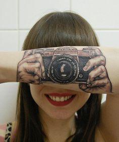 """A fotógrafa holandesa Lotte van der Acker, 24, tem em seu braço uma tatuagem que é uma ilusão de ótica. A imagem, que simula que ela está usando uma máquina fotográfica, foi feita pela tatuadora e mãe da jovem, Helma van der Weide. O desenho é a reprodução do modelo Pentax Asahi 35mm dos anos...<br /><a class=""""more-link"""" href=""""https://catracalivre.com.br/geral/fotografia/indicacao/camera-tatuada-em-braco-cria-ilusao-de-otica/"""">Continue lendo »</a>"""