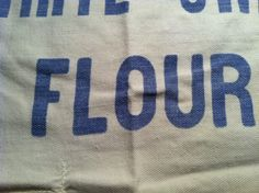 """""""Flour"""" close up. I love the quality of the thin blue ink on the uneven vintage fabric. Nice typography, too."""