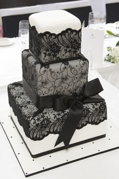 White wedding cake with black lace and a bow. Cute, and won't leave teeth green/black like black frosting!
