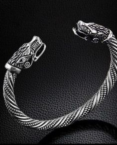 Viking Dragon Head Silver Bracelet, Norse, Reenactment Pagan. This Dragon Headed Bracelet is handmade. It is based on a bracelet found in Sweden that is around 1000 years old. It weighs 24g and has an internal length of 16cm, plus a small gap between the terminals.This bracelet is designed to be worn loose and adjustable only once. Please bend with gentle and even pressure so that you can slide the bracelet onto your wrist.
