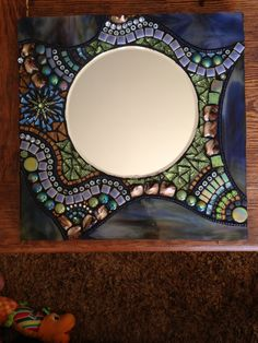 I used a swirling blue,green and brown stained glass piece around the edges and added to it lots of beautiful cut glass, beads ,millefiori