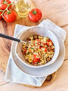 Tomatiger Bratreis mit Käse - Mit vollreifen Tomaten, mildem Olivenöl, pikantem Knoblauch, einer Prise Salz und würzigem Käse verwandeln Sie den sonst eher faden Reis in eine wohlschmeckende Hauptmahlzeit.