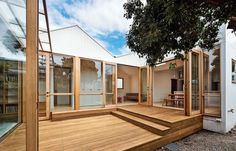 The addition is clad in grooved painted plywood and the new deck is made from blackbutt wood, the sort used for wharves