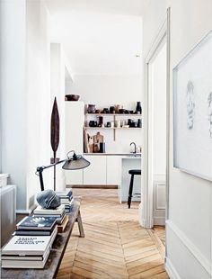 Beautiful all-white Paris apartment will mouldings, parquet herringbone floors and contemporary furnishings.