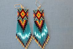 "Here is a really stunning pair of long beaded earrings I made. The turquoise blue satin bugles make them just shine, along with the gold. I call them, ""Rio Grande"""