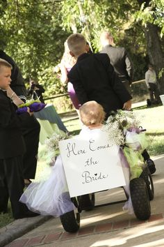 Here Comes the Bride sign attached to a wagon for the little guys