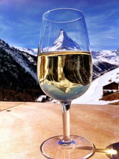 Mountain reflection through a glass of white wine on the terrace of one of Zermatts greatest restaurants Chez Vrony. Switzerland