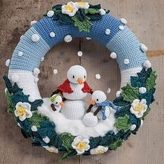 Winter Wreath Crochet a charming scene of snow mommy and her two children having a blast in the freshly fallen snow between beautiful Hellebores flowers and Holly and Ivy leaves. A beautiful, very detailed pattern to create your own winter wreath. Crochet Christmas Wreath, Crochet Wreath, Crochet Snowman, Crochet Christmas Decorations, Christmas Crochet Patterns, Xmas Wreaths, Christmas Knitting, Christmas Crafts, Christmas Ornaments
