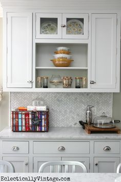 Wire basket for cookbooks//White kitchen - love the open shelves and the fun collections.  eclecticallyvintage.com