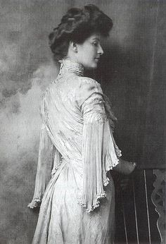 """Miss Sedley wears a delicately pleated, draped, high-necked gown, 1903. The twisting lines of the bodice emphasise the corseted curves of her silhouette, and her high collar would have been held up by wire of whalebone. Hairpieces and hair pads were often used to create the required volume, and hair was held in place with combs."" Scanned from ""Decades of Fashion"" by Harriet Worsley."