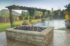 This extra-large rectangular fire pit is almost the width of the pool. The pool, patio, trellis, and fire pit were all installed by Red Valley Landscape & Construction.