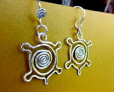 Turtle Spiral Tribal Charm Earrings in Sterling Silver on French Earrings These turtle earrings are super cute, fun, and perfect for any animal/turtle lover. Their fun tribal design features four cute legs and a tail centered with a spiral. The turtles round head hangs from a jumpring, and then the earwire, allowing for the turtle to swing freely from the ear. These playful earrings are sure to be a favorite, made of shiny hammered sterling silver. They are unique and are sure to gain co...