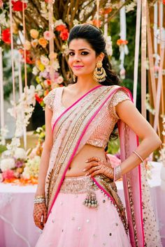 Indian bride wearing pink bridal half saree. #StatementEarrings #IndianFashion