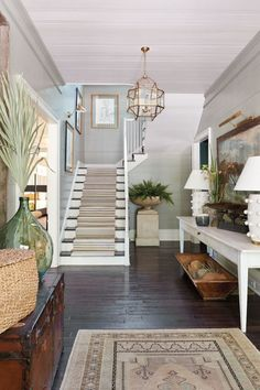 Summer style!! Cool and elegant front hallway foyer with gray painted wood plank on the walls - lots of gorgeous useful furniture and plants too! Just a perfect front hallway! And white modern lamps on a white console table!