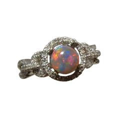 Ladies Semi Black Opal ring with diamonds in 14k Gold.
