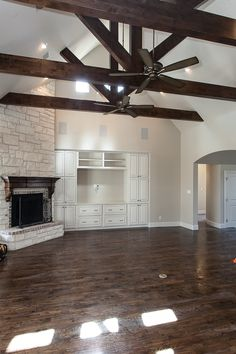 """Gorgeous Hand scraped Red Oak Floor, 42"""" wood burning fireplace with floor to ceiling stone surround.  Round bullnose wall corners and custom built in entertainment center.  Beautiful wood beams draw the eye up designed by Cleve Adamson.  www.cleveadamsoncustomhomes.com"""