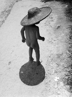 """P'tit homme à l'ombre d'un immense """" chapeau d'paille, paille, paille... """"/ By Werner Bischof."""