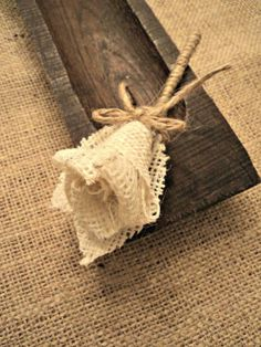 Burlap flower or rosebud. I'd consider a twig stem. No link for DIY, but an opportunity to get creative!