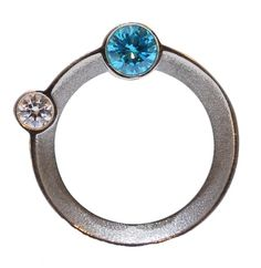 This distinctive sterling silver ring features semi precious stones set on the side of the ring orbiting around the finger creating flashes of colour when worn. -£330