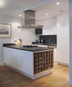 Our Handleless kitchen design in white high gloss lacquer with bespoke oak winerack.