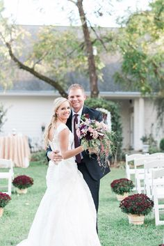 The bride and groom stand in the aisle at their Matthews House wedding among white chairs and red flowers. The bride holds a bouquet of purple and pink flowers. Flowers by Flowers on Broad Street, gown by Oleg Cassini, photos by J Parker Photography. NC wedding inspo.