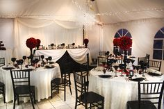 Black and white wedding reception with pops of red with roses