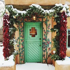 A beautiful door on Canyon Road adorned with chile ristras, evergreens and snow. Mexico Christmas, Christmas Door, Christmas Stuff, Christmas Trees, New Mexican, Mexican Art, Travel New Mexico, New Mexico Style, Spanish Holidays