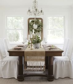Lighten up a heavy table w/ slipcovered chairs - A Pottery Barn runner and Target slipcovers lighten up the heavy oak dining-room set in this century-old Oregon farmhouse. Read more: Dining Room Decorating Ideas - Dining Room Decor - Country Living Easy Christmas Decorations, Christmas Table Settings, Holiday Tables, Winter Decorations, Holiday Wreaths, Room Decorations, Wreaths Crafts, Christmas Tables, White Farmhouse