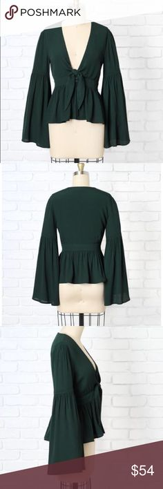 Emerald Green Statement Sleeve Blouse Statement sleeves continue to be a chic trend this season. Keep up with the style by opting for this pretty emerald green-hued blouse, designed with a breezy fabric in a fitted silhouette. Made with a peplum hem for a feminine touch, this top features a tie-front neckline and small buttons up the front, and is finished with flowy wide sleeves.—DR-00270 Dorimas Closet Tops Blouses
