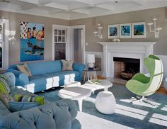 Living room by Ghislaine Vinas with light blue tufted Chesterfield sofa, modern white coffee table, classic Egg chair and a white fireplace